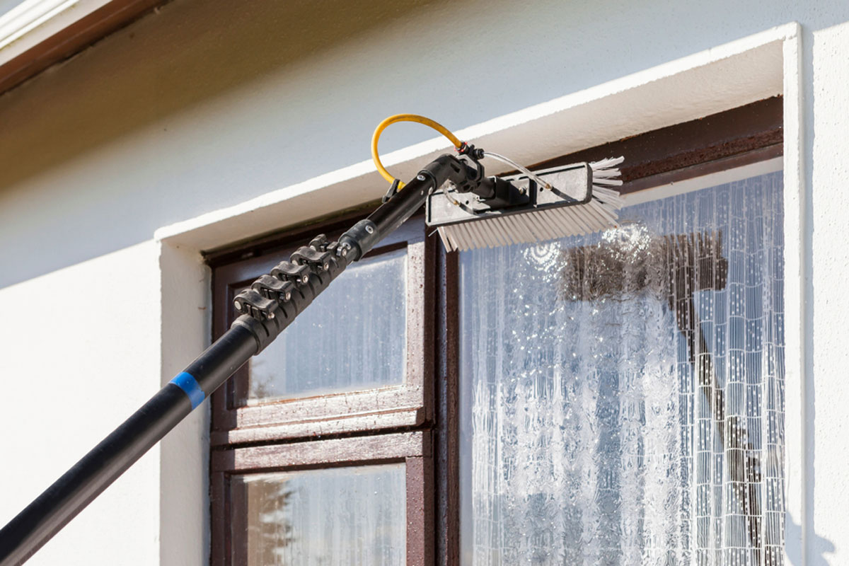 Window Cleaner Removing Dirt and grime from 2nd story window with Telescopic water brush