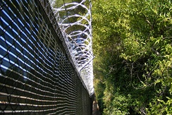 A chain-link privacy fence topped with razor wire protecting a utility power substation.