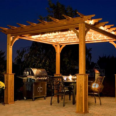 Illuminated, classic style, pergola with outdoor dining area on a stone patio.